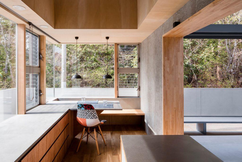 Home office. Escritorio de madera y silla. Dos lámparas colgantes. Pisos de madera. Grandes ventanales con vista a un jardín.