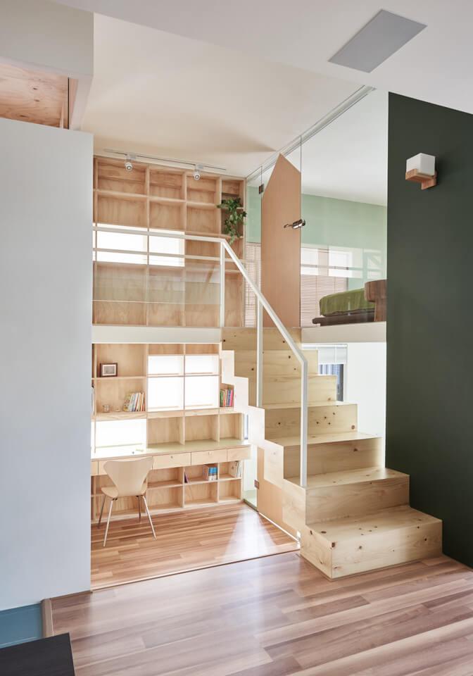 escritorio, estantes y silla de madera al lado de una escalera. Home office