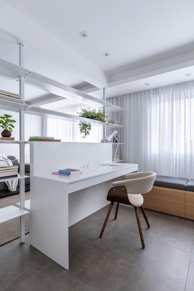 Escritorio con estantería que divide un ambiente en dos. Home office.