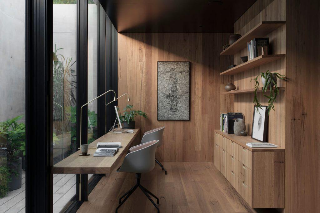 Home ofice. Escritorio de frente a un ventanal que da a un patio interno. Dos sillas y dos lámparas. Pisos de madera.