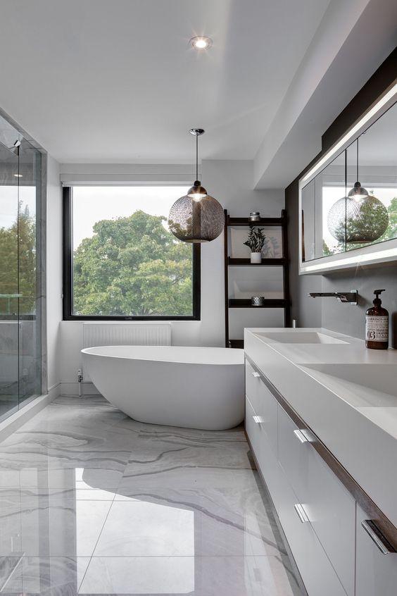 Baño con pisos de marmol, tina de cerámica y un ventanal con vista a un bosque - tendencias de arquitectura