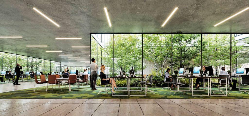 Renderización de proyecto de oficinas. Personas trabajando en computadoras. Patio interno con mucha vegetación. Biofilia.